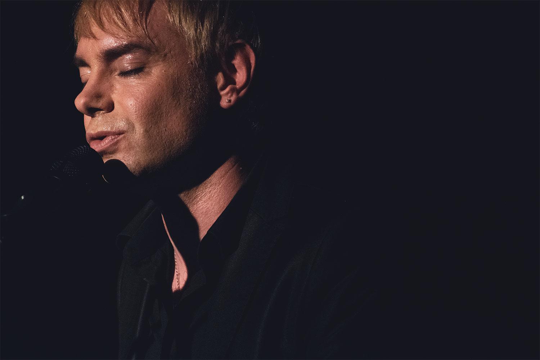 Jean Andreu en concert yeux fermés devant un micro, fond noir, attitude sereine et romantique